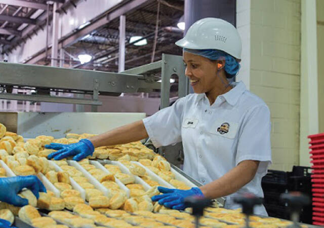A factory worker sorts buns on a production line